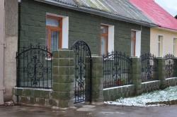 Дом, огражденный кованым забором