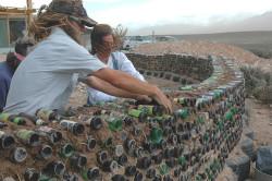 Заполните бутылки песчаной смесью и закрутите крышки. Начинайте выкладывать рядами и промазывайте каждый ряд цементным раствором.