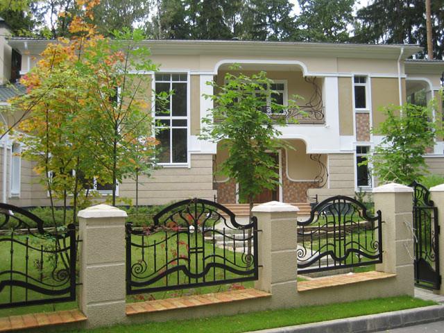 Дом с забором из ковки и камня